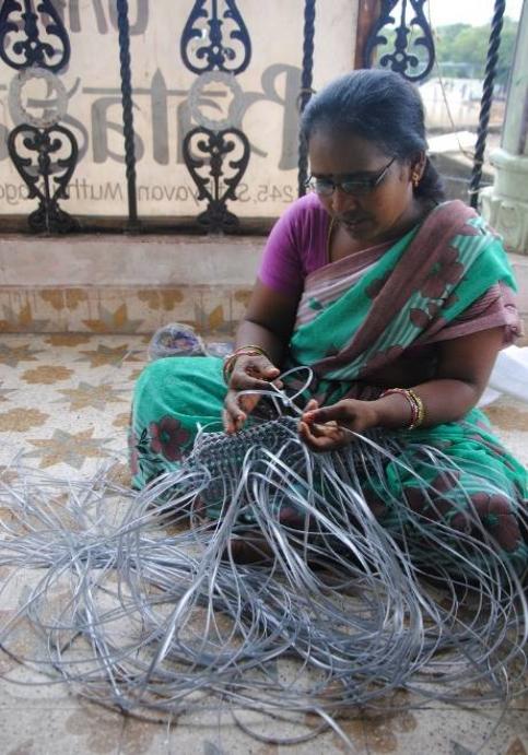 L'une des employées de Speed Trust, en train de confectionner un panier en plastique recyclé. © AR